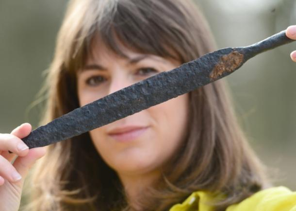 Map Archaeological Practice Ltd staff member Sophie Coy holds a spear head that was found at the site