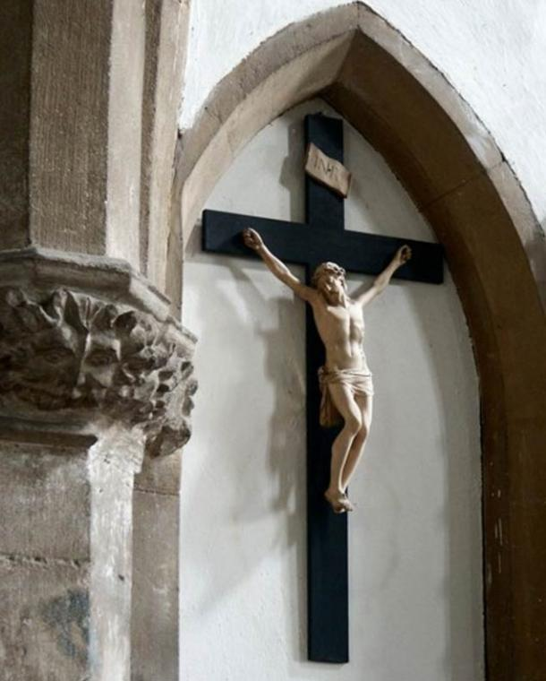 Pre-Christian symbol of a Green Man sits alongside a Christian statue of Jesus, St John the Baptist, St Michael & All Angels