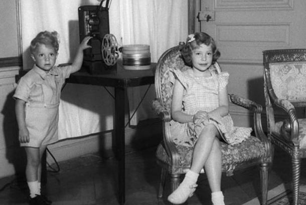 A young Princess Christina and her brother see a film in one of their rooms at Drottningholm Palace.