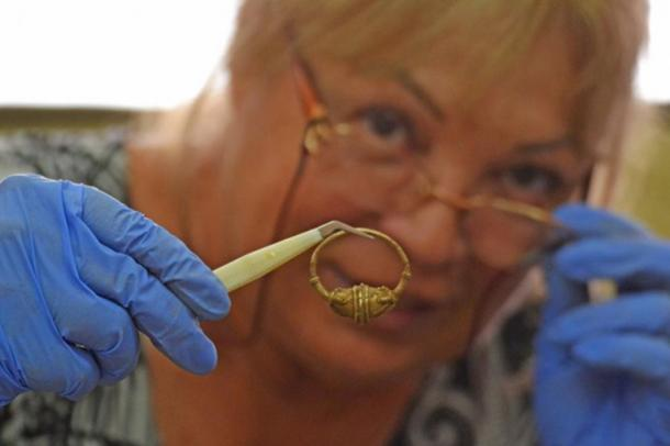 Professor Bonnie Petrunova inspects one of the pieces of jewelry. (Image: National History Museum, Bulgaria)