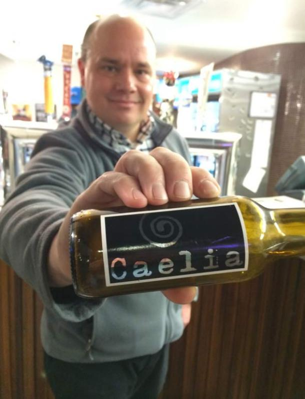 Colorado State University Professor Jonathan Carlyon with a bottle of caelia from a Spanish microbrewery