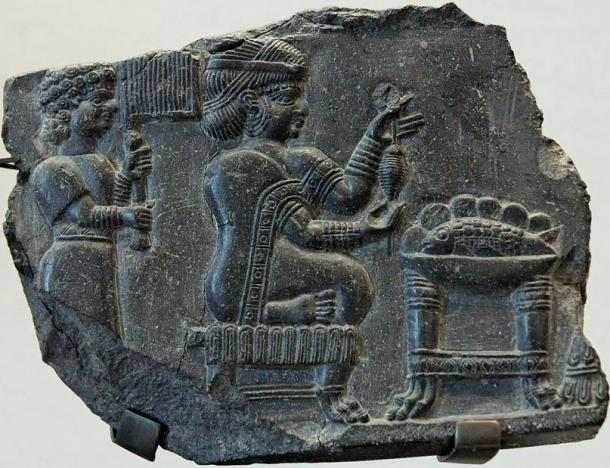 Relief of a woman being fanned by an attendant while she holds what may be a spinning device before a table with a bowl containing a whole fish. Circa 700 - 550 BC, Susa. Representational image.
