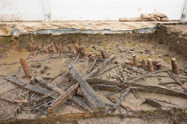 Remains of a house at Must Farm showing the unburnt stumps of posts under the waterline during the fire (top-right) and collapsed joists