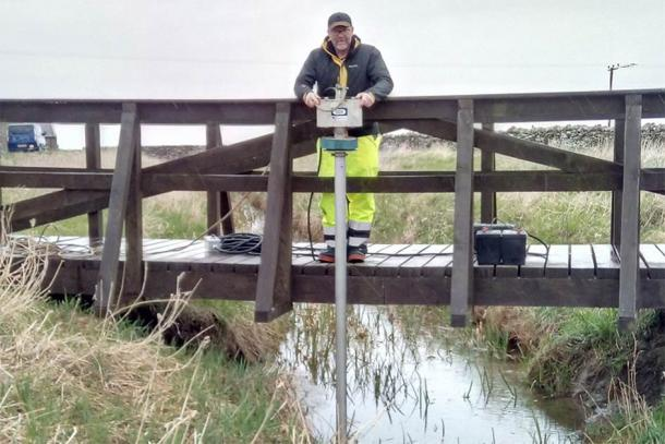 """One of the researchers taking sediment samples in the """"mapping"""" of the Orkney Viking waterway. (University of Saint Andrews)"""