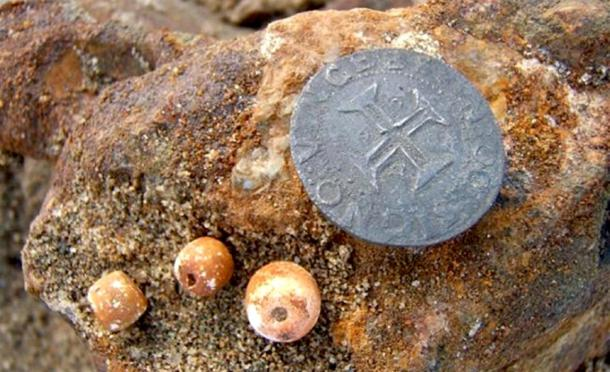 Rosary beads and a silver Portuguese coin that were found with the wreck.