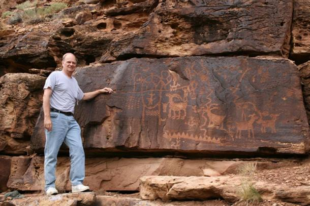 John A. Ruskamp stands near petroglyphs that match ancient Chinese script in Nine Mile Canyon, Utah.