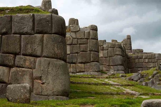 """The ruins of the Inca temple fortress of Sacsaywamán, meaning """"Contented Falcon"""" in Quechua. The defensive perimeter of this temple and other Inca defense systems often made use of giant stone blocks like these, some of which weigh more than a few tons (thousands of kilograms). The largest Inca stone block ever recorded weighed 70 tons or about 70,000 kg! (McKay Savage from London, UK / CC BY 2.0)"""