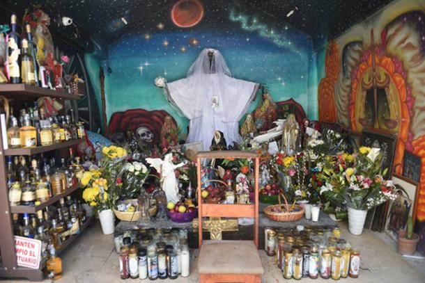 Santa Muerte shrine (©Toni François) Different colored candles are lighted for specific requests or purposes. A brown candle is for wisdom, a white candle for gratitude, a black candle for protection and vengeance, and more.