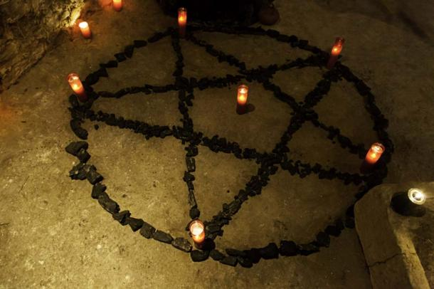 Satanic pentacle with candles in a dark ritual (esebene / Fotolia)