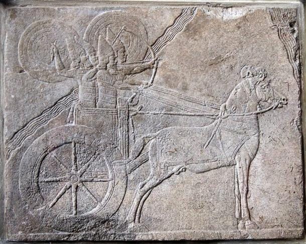 Scene from Ashurbanipal (668-627 BC) campaign against the Elamite city Hamaru, shows an Assyrian chariot with charioteer and archer protected from enemy attack by shield bearers. Assyrian relief from Nineveh. Alabaster relief, made about 650 BC.