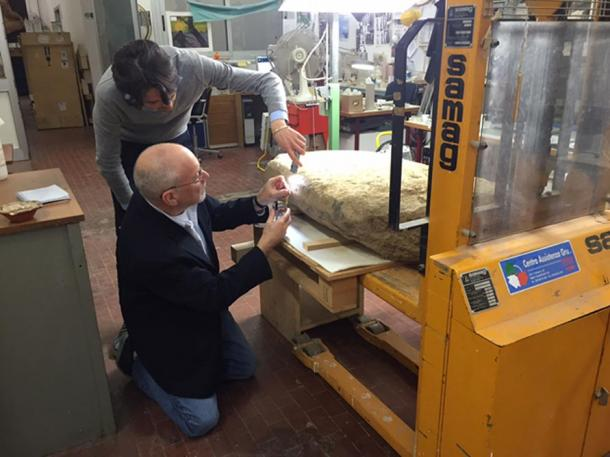 Scientists examine the Etruscan stele.