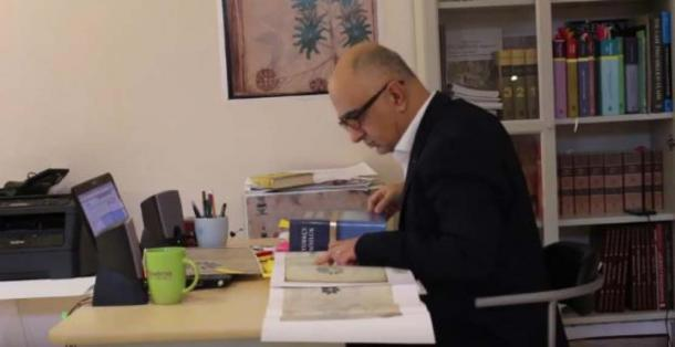Screen shot from promotional video showing Mr. Ardic researching a copy of the Voynich Manuscript. (Voynich Manuscript Research/YouTube Screenshot)