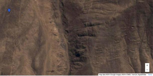 Screenshot from Google Maps showing long band of holes at left, and indications of a settlement to the right
