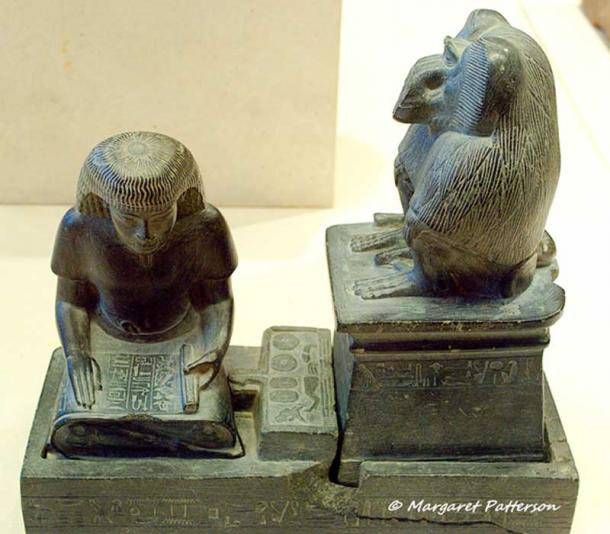Scribe Nebmerutef is portrayed under the attentive gaze of the god Thoth, patron of writing. He is engrossed in reading a document, seated cross-legged on the ground, with his torso leaning slightly forward, and his right hand resting on the papyrus. Above him, the baboon sacred to Thoth is seated on a pedestal. New Kingdom. Louvre Museum, Paris.