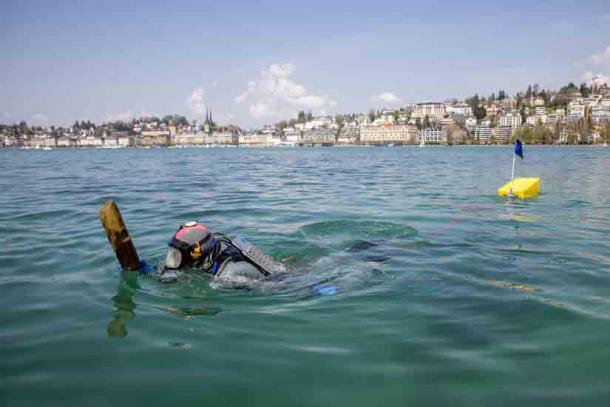 A scuba-diving archaeologist brings a part of the stilt house village found beneath Lake Lucerne to the boat. (Canton Lucerne)