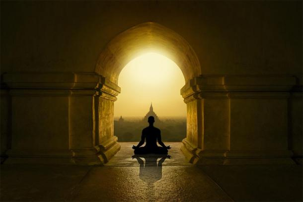 Silhouette meditating in Buddhist temple. (quickshooting / Adobe stock)