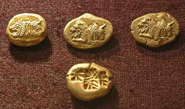 """A number of """"staters"""" (a standard measure) from the sixth century BC from a hoard found in Clazomenae. The central """"lion and bull"""" one is thought to come from Lydia. (Dosseman/CC BY-SA 4.0)"""