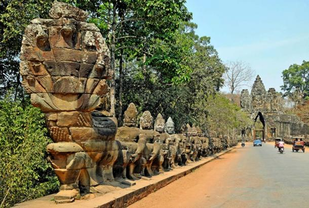 Statues at the South Gate of Angkor Thom in Cambodia, with gods holding the 9-headed serpent.