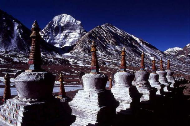 Stupas, with the north face of Mount Kailash in the background – both are symbols of axis mundi.