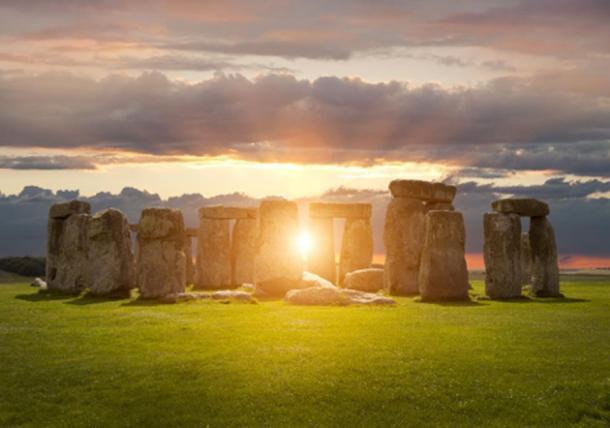 Sun shining through Stonehenge. (andrewmroland /Adobe Stock)