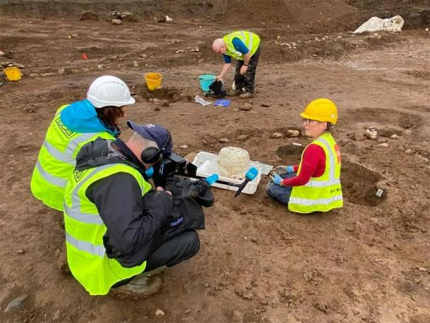 Susannah Kelly (on the right), a specially trained archaeological conservator, showing RTE reporters the successful removal of the urn from the earth and clay it was surrounded by. (Fadó Archaeology)