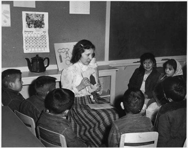 Teacher with picture cards giving English instruction to Navajo day school students. (US National Archives / Public Domain)