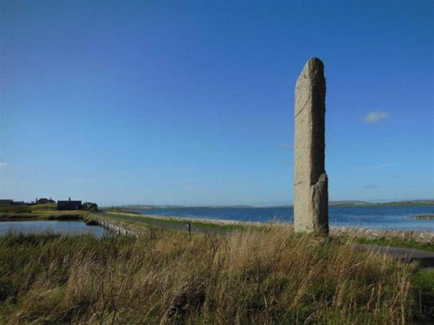 The 5.6 meter tall Watchstone on the Orkney Mainland and behind it the isthmus dividing Loch Stenness (left) and Loch Harray (right). This enormous stone pillar once formed part of an almighty avenue of stones. (Image: © Andrew Collins).