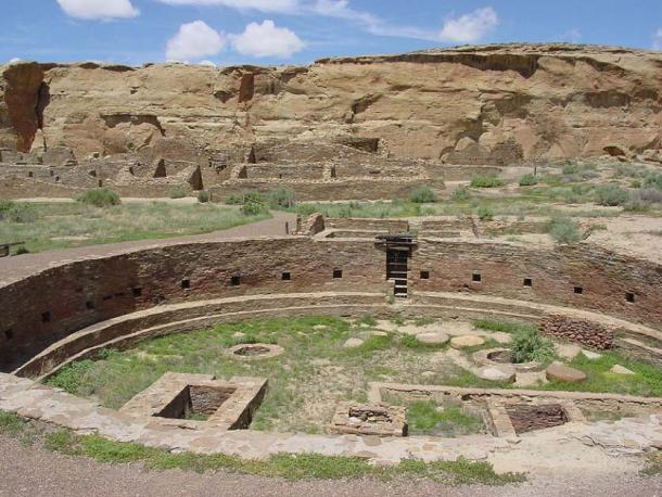 The Chaco Canyon 'Chetro Ketl' great kiva plaza is a vast circular depression outlined by a stone wall with a great sandstone cliff towering in the background. (Public Domain)