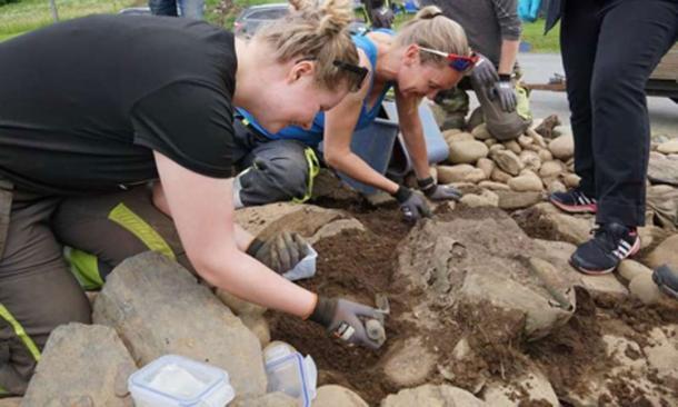 The cauldron has been uncovered, and Heidi Fløttum Westgaard, Ellen Grav Ellingsen and Kjell André Brevik carefully clean it off. (Astrid Kviseth / NTNU University Museum)