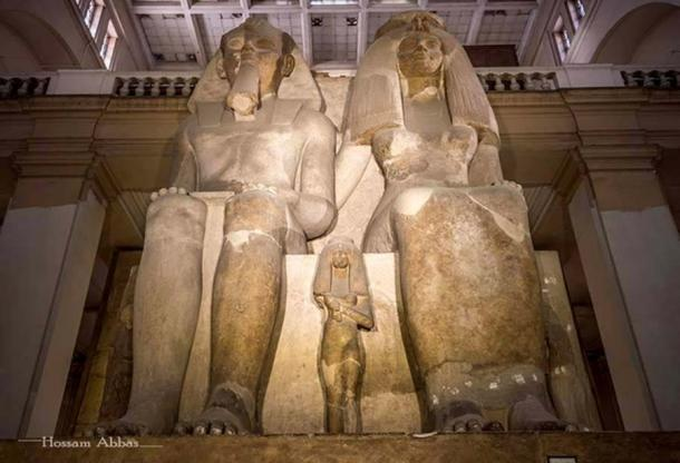 The colossal limestone group statue of Amenhotep III, Queen Tiye and their daughters – Henuttaneb, the largest and best preserved, in the center; Nebetah on the right; and another, whose name is destroyed. The sculpture rises seven meters in height dwarfing all other statues in the central hall of the Egyptian Museum, Cairo. This monolith originated from Medinet Habu in Western Thebes.