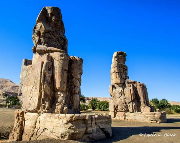 """The gigantic Colossi of Memnon, made of quartzite sandstone, depict the enthroned Pharaoh Amenhotep III in the first pylon of the """"Temple of Millions of Years"""" in the Theban Necropolis. Kom el-Hetan, near Luxor."""