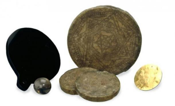 The magical tools of John Dee: golden and wax discs, a quartz sphere, and a polished mirror.