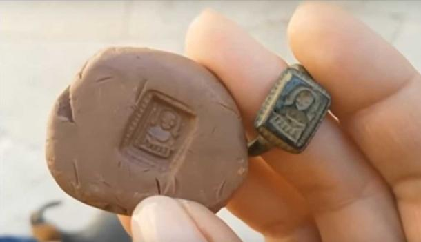 The medieval St Nicholas ring with its impression in clay. (Youtube Screenshot)