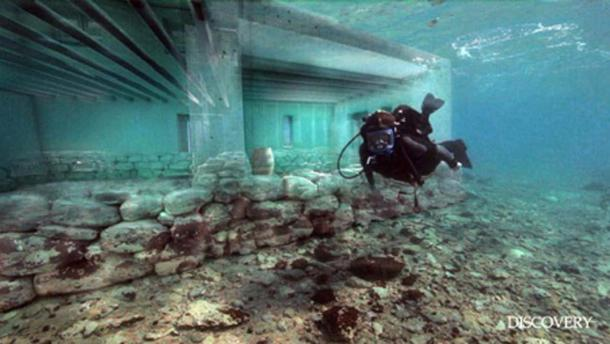 The original foundations of the city underneath the reconstructed pillars and walls of one of the buildings. (Discovery)