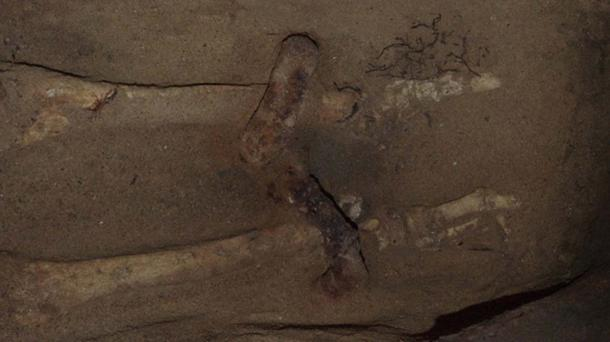 The shackles around the skeleton's ankles.