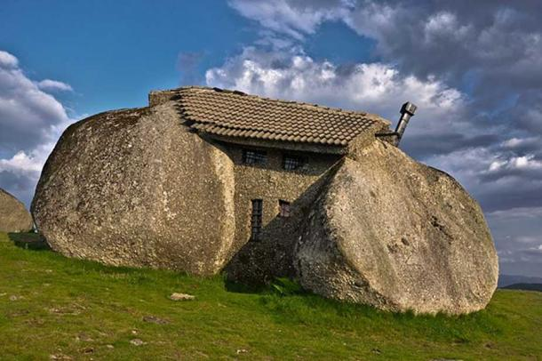 The stone house in Portugal, with visible bars on the windows.