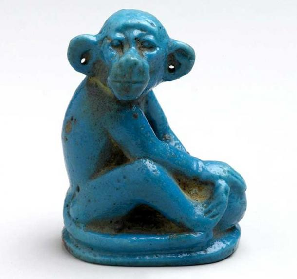 This blue glazed faience monkey seated on an ovoid base holds a round object, perhaps a ball or a piece of fruit, in its forepaws. In antiquity the animal's pierced ears had metal earrings indicating that it was a household pet. 18th Dynasty. Tell el Amarna. Brooklyn Museum, New York.