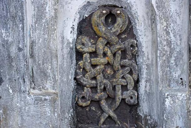 Two entwined snakes stand at one end of the wall, near Gorakhpur, India.