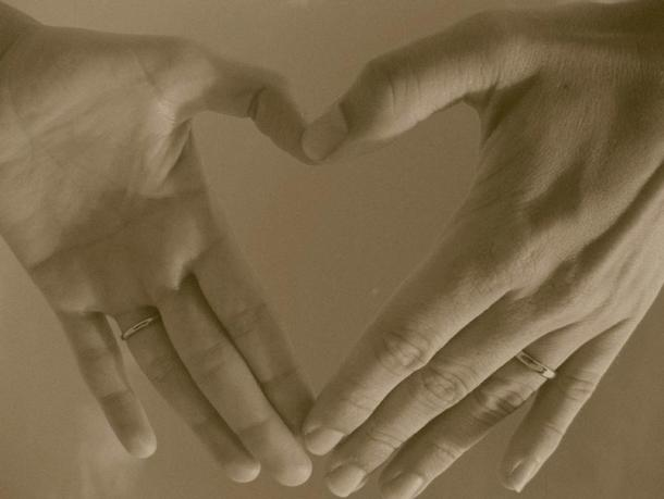 Two left hands forming an outline of a heart shape. Both hands are wearing a wedding ring.