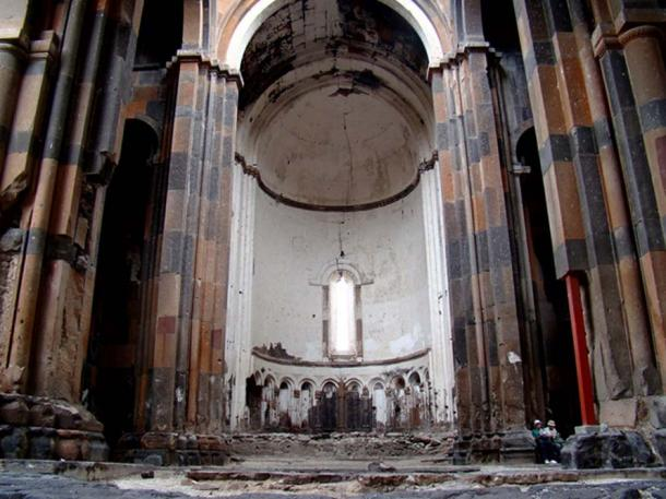 Two people sitting inside the Cathedral of Ani just a hundred metres from the border of Armenia. Large parts of the roof have fallen down, allowing daylight to find its way into the building.