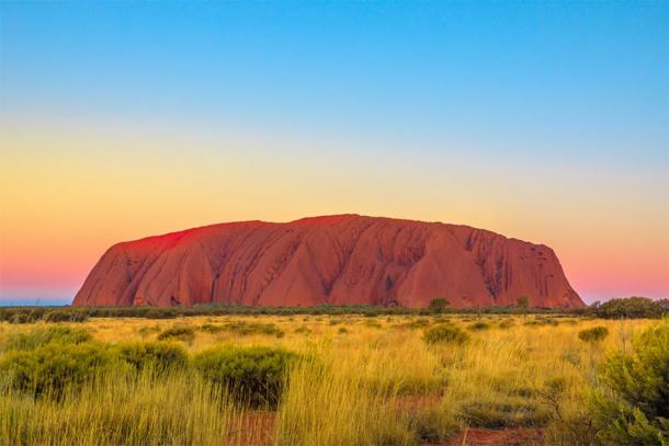 Shot of Uluru just after sunset, where the Aboriginal rock art can be found. (bennymarty / Adobe stock)