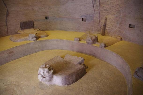 """View of the reconstructed bas-reliefs and rock-cut benches inside the """"House of the Eagles"""". Three seats sculpted in the shape of a jaguar skin and eagles with sprayed wings surround a central altar also in the shape of an eagle. A circular hole in the floor would have served to collect blood or other liquids from the altar. It is also possible that the circular hole, filled with water, could have served as a water mirror for solar or astronomical observations. (© Marco Vigato)"""