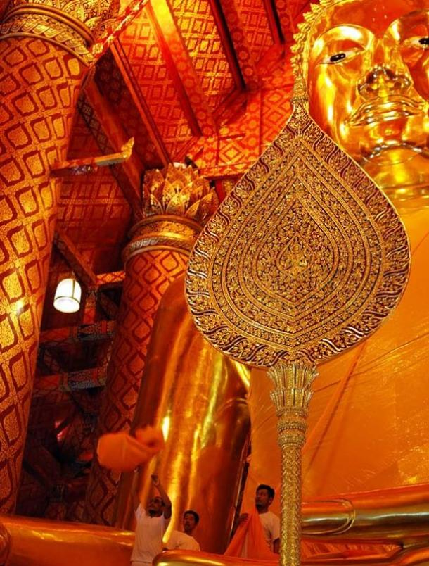Wat Phanan Choeng, from 1324 CE, houses an immense seated gilded Buddha. Folded orange lengths of cloth are thrown up from the ground to people who are standing in the Buddha's lap. The robes are then unfolded and rolled out from above over the worshippers below as a form of blessing
