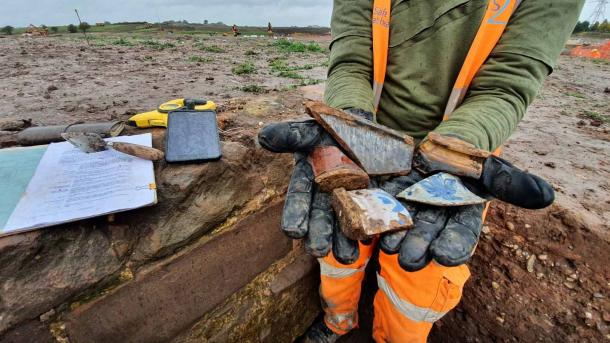 A Wessex archaeologist holds up post-medieval-era pottery found at the Coleshill Manor site. (HS2 Ltd.)