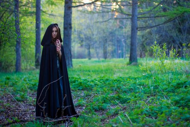 Wise Woman in black cloak in the forest