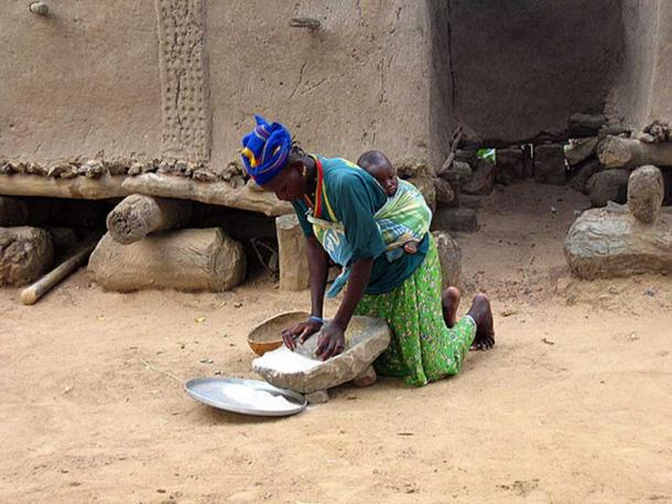Woman grinding flour in front of traditional Dogon grain storage sheds.