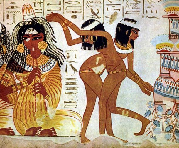 Women entertainers perform at a celebration in Ancient Egypt; the dancers are naked and the musician wears a typical pleated garment as well as the cone of perfumed fat on top of her wig that melts slowly to emit its precious odors; both groups wear extensive jewelry, wigs, and cosmetics; neither wear shoes - Thebes tomb c. 1400 BC.
