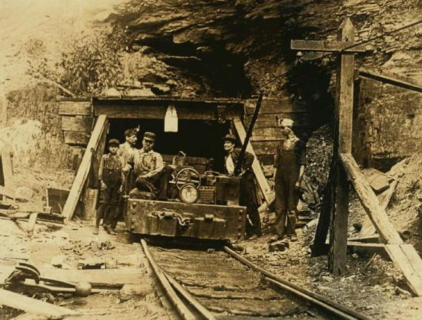 """Workers at the entrance to a W. Va. coal mine: a """"drift"""" mine. (Public Domain)"""