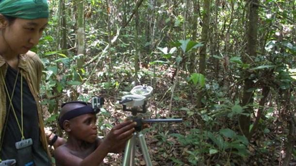 Young Mbendjele boy of age 8.5 years pointing at a food location. Here with researcher Haneul Jang in the tropical rainforest of the Republic of Congo. (© Karline Janmaat)