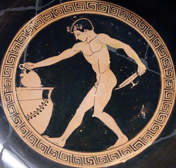 Youth using an oinochoe (wine jug, in his right hand) to draw wine from a crater, in order to fill a kylix (shallow cup, in his left hand). His nudity shows that he is serving as a cup-bearer in a symposium, or banquet.